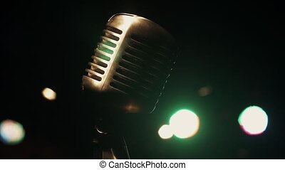 Concert metal glitter microphone stand on stage in retro club. Green spotlights.
