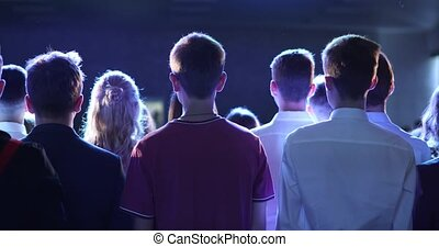 Crowd of people fans at music concert in blue light of spotlight, back view.