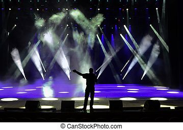 Concert stage - Singing man silhouette on a brightly lit...