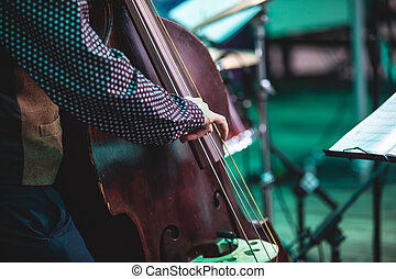 Concert view of a contrabass violoncello player with vocalist and musical during jazz orchestra band performing music, violoncellist cello player on stage
