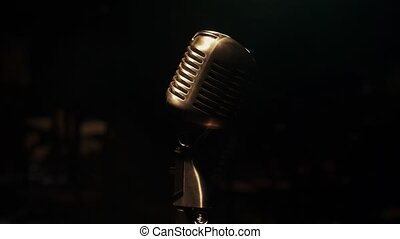 Concert vintage glitter microphone stand on stage in retro club. Spotlight.