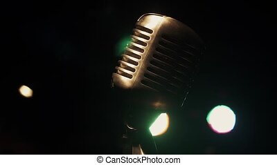 Concert vintage glitter microphone stand on stage in retro club. Green spotlight