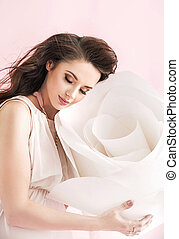 Concetpual image of brunette woman cuddling a giant rose