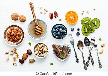 concetto, arancia, cibi, set, mandorle, chia, ingredienti, lay., fondo., fondo, frutte, mirtillo, appartamento, cibo, noci, bacche, noci, miele, .the, bianco, sano, su, legno, semi