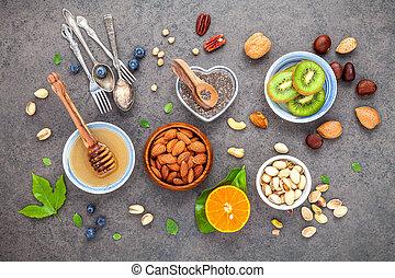 concetto, arancia, cibi, set, mandorle, chia, ingredienti, fondo., fondo, frutte, mirtillo, appartamento, cibo, noci, bacche, noci, miele, .the, scuro, pietra, sano, su, semi, disposizione