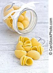 Conchiglie pasta raw on wooden background