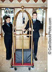 Concierge colleagues holding baggage cart with luggage on it