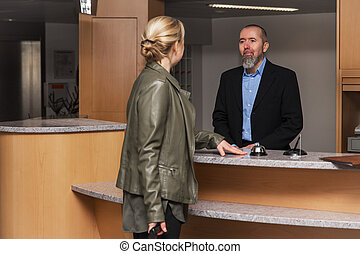 concierge in a hotel is smilling to an female guest