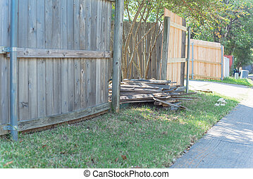 Concrete back alley with old fence near new lumber boards pickets at suburban residential house in Texas, USA