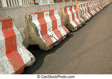 heavy concrete barricade seperating traffic lanes on track
