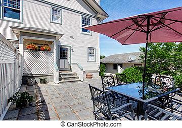 Concrete floor cozy patio area with table set and patio umbrella.