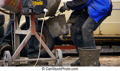 Concrete Mixer Builders and People Working at a Construction Site. Slow Motion