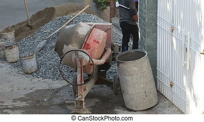 concrete mixer mixes cement solution in street near building...