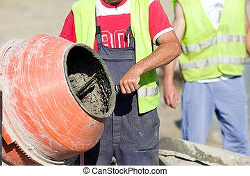 Concrete mixer on construction site - Construction worker ...