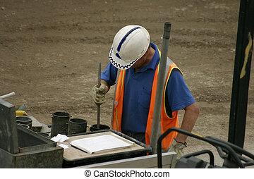 Concrete moulds - a man stomps concrete into moulds on a...