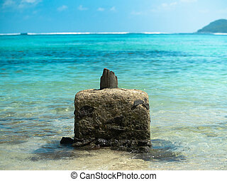 Concrete outcropping with remains of a wooden pillar off a ...