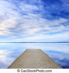 Concrete pier or jetty and on a blue lake and sky reflection on water.