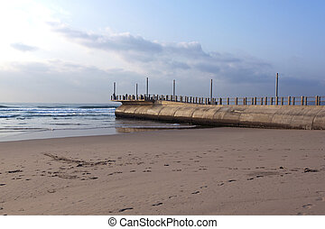Concrete Pier Protruding from Sea at Low Tide