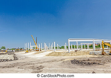 Concrete pillars of new edifice with a beautiful sky are placed on sandy ground