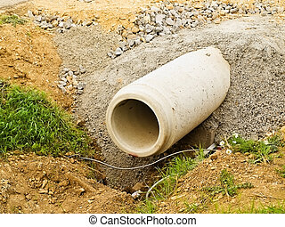 concrete pipe on the building to drain excess water and connecting trenches