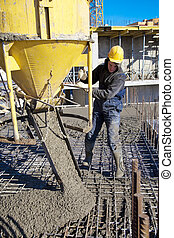 Concrete pouring works - Builder worker in hard helmet and ...