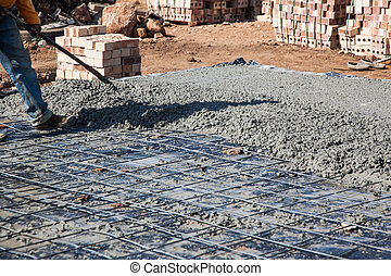 Concrete slabspreading by worker
