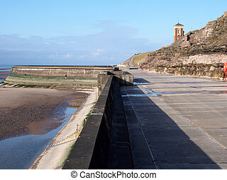 concrete stairs on seawall in blackpool with the beach at low tide in sunlight with the old boat pool and tower in the difference