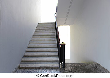 Concrete Stairs with white walls, wooden handrail