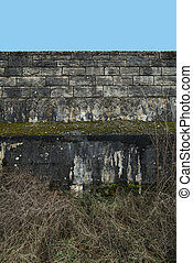 Concrete wall with stones and jutty in front of blue sky