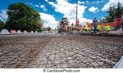 Concrete works for road construction with many workers and...
