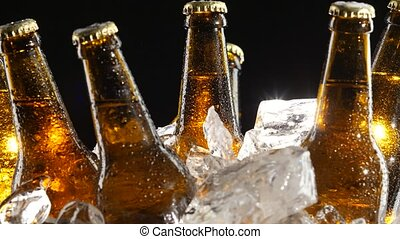 Condensate flows down the brown glass of bottles from beer....