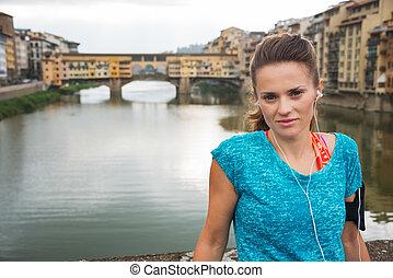 condición física, mujer, con, auriculares, permanecer, frente, de, ponte vecchio