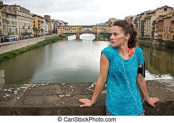 condición física, mujer estar de pie, delante de, ponte vecchio, en, florencia, él