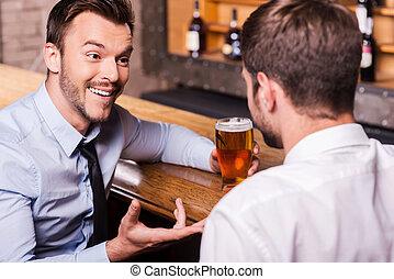 condivisione, birra, con, buono, friend., due, allegro, giovani uomini, in, camicia cravatta, parlando, altro, e, gesturing, mentre, bere, birra, a, il, sbarra contraddice