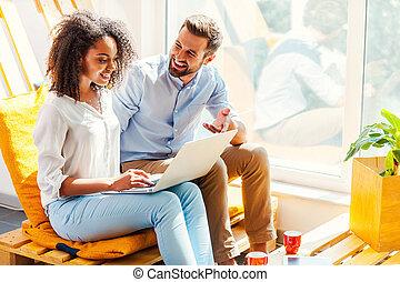 condivisione, loro, ideas., sorridente, giovane, donna africana, lavorando, laptop, mentre, equipaggi seduta, appresso, lei, in, il, zona resto, di, ufficio