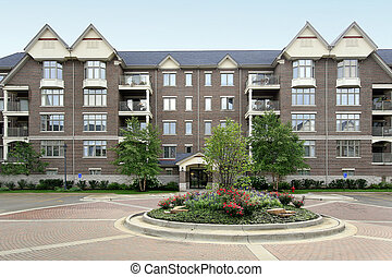 Four story condominium building with circular brick drive