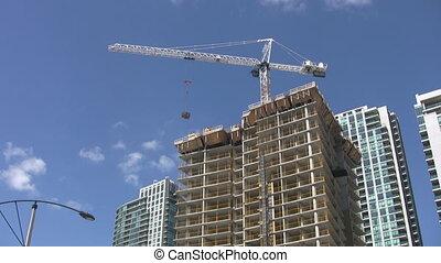Real time shot of condominiums under construction. Tower crane swings around. Toronto, Ontario, Canada.