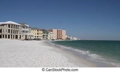 Homes and condominiums stretch along the white sandy coastline of Destin Beach, Florida.