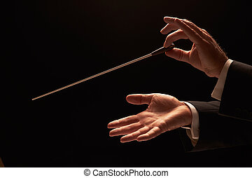 Conductor conducting an orchestra isolated on black ...