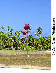 Cone wind measure wind direction in small airfield on the tropical island with palm trees at a runway