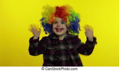 confection, avoir, faces, coloré, peu, clown, fille souriant, danser., perruque, amusement, halloween, idiot, enfant