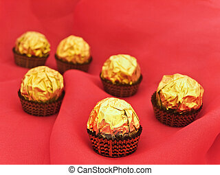 confection in golden candy wrapper at red textile background...