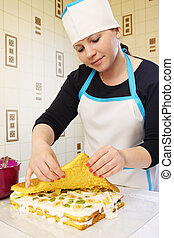 confectioner collects cake - Sponge cake smeared cream with...