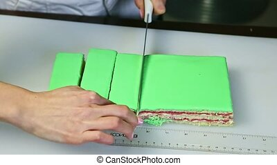 confectioner cut out on portions by knife green glazed cake ...