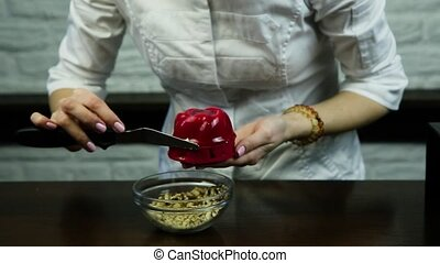 confectioner decorate red glazed dessert with crushed nuts -...