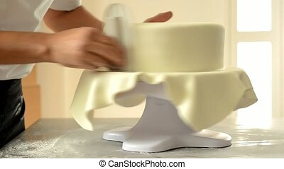 Confectioner decorating a wedding cake with white fondant. -...