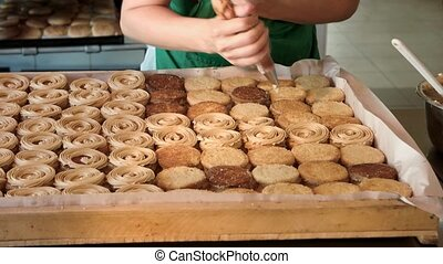 Confectioner decorating biscuits with yummy cream. Baker...