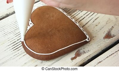 Confectioner decorating heart-shaped biscuit. Piping white...