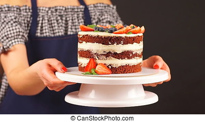 Confectioner girl holds two hands a delicious cake.