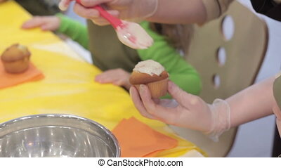 Confectioner glazing  cupcake using pastry brush